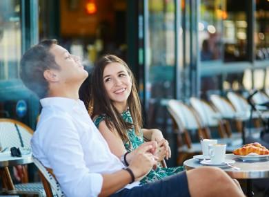 A young couple smoking outside a café in Paris.