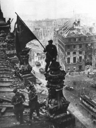A Soviet soldier holding the national flag atop the Reichstag in Berlin in 1945