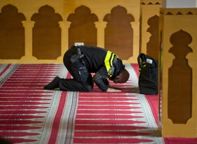 A Dutch police officer prays at the Al Kabir mosque in Amsterdam.