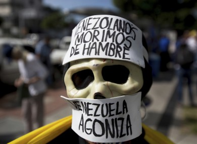 A demonstrator wears a skull mask with messages that read in Spanish: