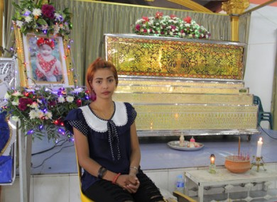 Chiranut Trairat sits in front of her daughter's coffin at Si Sunthon temple in Phuket, Thailand