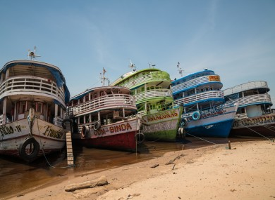 Five boats moored on the banks of the Amazon river in Brazil.