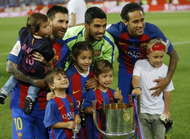Barcelona's Lionel Messi, left, Luis Suarez, center and Neymar pose with the trophy and their children after the Copa del Rey final.