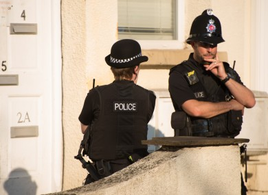 Police officers guard a residence in Manchester.