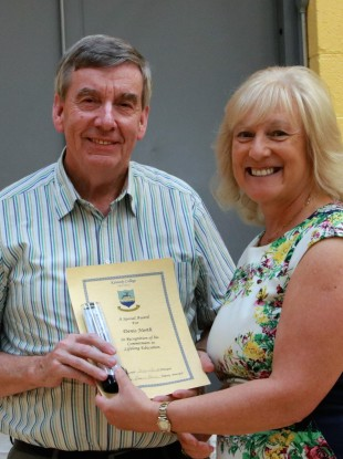 Denis North receiving an achievement award for lifelong learning from principal Suzanne Barrett at Kennedy College