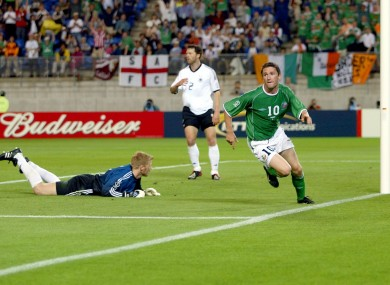 Robbie Keane takes off in celebration as Germany's Oliver Kahn looks on in dismay.