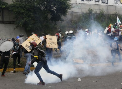 Government forces launching tear gas at demonstrators in Caracas yesterday