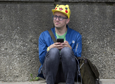 Ryan Copple of Los Angeles sits in the shade as he struggles to play Pokemon Go at the Pokemon Go Fest in Chicago.