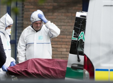 A member of the Garda Forensic Team looks on as the body of the three-year-old boy is placed in an ambulance on Tuesday.