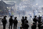 Palestinians run away from tear gas in Jerusalem yesterday