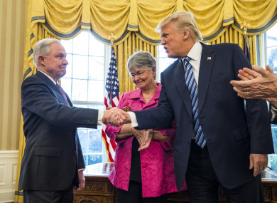 US President Donald Trump  shakes hands with Attorney General Jeff Sessions