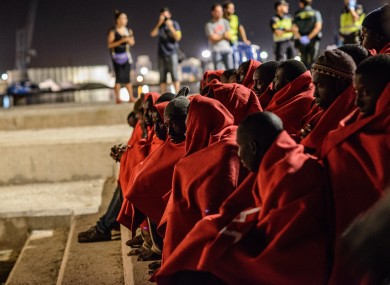 52 migrants, among them a woman and two boys, huddle on shore after being rescued by the Spanish Maritime last month.
