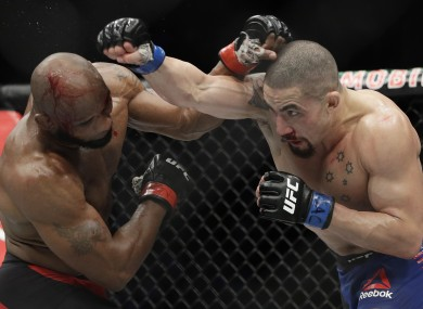 Yoel Romero, left, fights Robert Whittaker in a middleweight championship mixed martial arts bout at UFC 213.