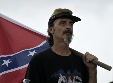 A man holds a Confederate battle flag.