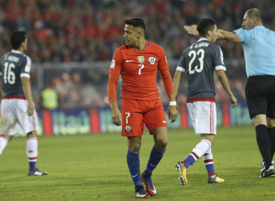 Chile's Alexis Sanchez, centre, walks on the field during a 2018 World Cup qualifying soccer match against Paraguay.
