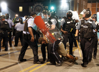 Police arrest a man as they try to clear a violent crowd.