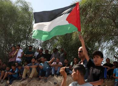 Palestinians celebrate as they wait for the arrival of Palestinian Prime Minister Rami Hamdallah and his government to take control of Gaza from the Islamist Hamas group.