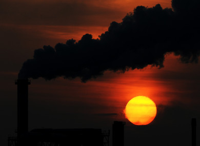File photo of the sun setting behind a smoking chimney of an industrial plant in Wismar.