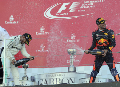 Hamilton sprays champagne at third placed Red Bull driver Daniel Ricciardo.