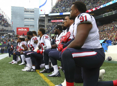 Rookie Carlos Watkins (91) and the rest of the Texans kneel during the anthem in Seattle.