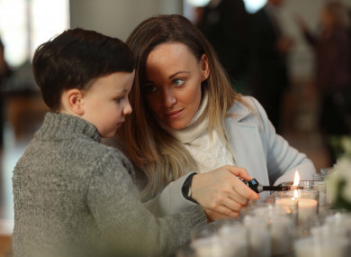 Lisa Marie Maher and her son Harry Foy (5) light a candle in remembrance of Harry's grandfather Eugene Maher.