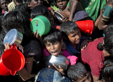 Rohingya children fighting to receive food handouts at a refugee camp in Ukhiya, Bangladesh.