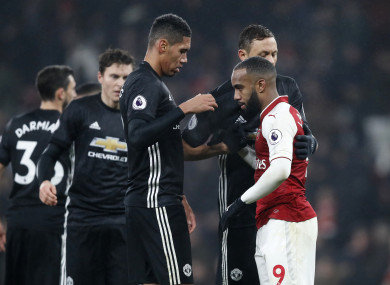 Chris Smalling shake hands with Arsenal striker Alexandre Lacazette.