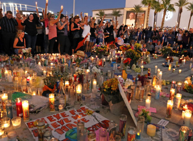People attend a candlelight vigil on the corner of Las Vegas Boulevard and Sahara Avenue