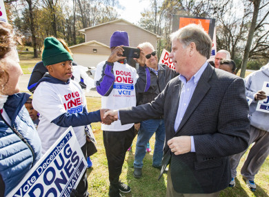 Democratic Senatorial candidate Doug Jones greets supporters as he campaigns outside the polls earlier today.