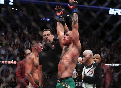 John McCarthy raises Conor McGregor's hand after his victory in the rematch with Nate Diaz at UFC 202.