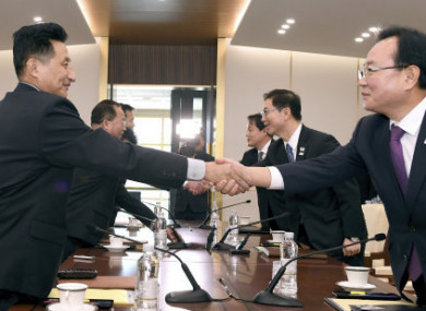 The South Korean delegation (left) and the  North (right) shake hands in the Demilitarised Zone.