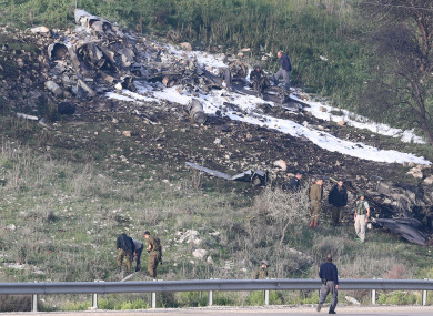 Israeli security personnel near the remains  of one of its fighter planes.