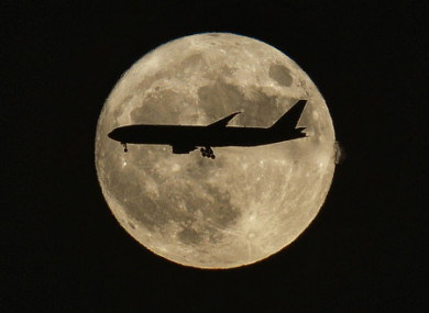 A plane flies past the 'supermoon' in Beijing, China.