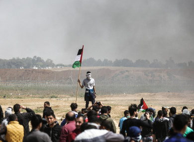 A Palestinian man holds his national flag as others burn tires to protect themselves from shots of Israeli soldiers at the Israel-Gaza border.