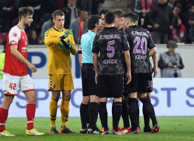 Freiburg players argue with the referee.