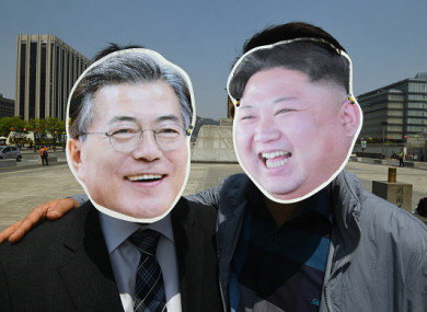 South Korean activists wearing masks of South Korean President Moon Jae-in (left) and North Korean leader Kim Jong-un (right) at a rally yesterday to support the upcoming Korean summit