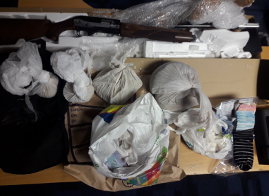 The shotgun and some of the drugs seized.