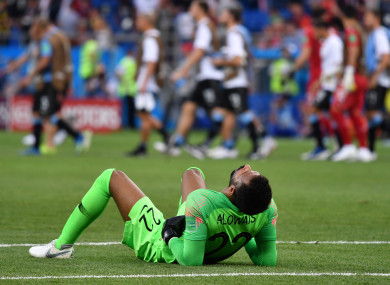 Saudi Arabia goalkeeper Mohammed Alowais lies on the ground after the final whistle.