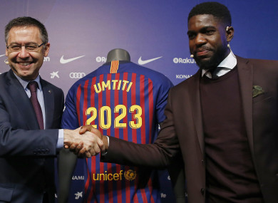FC Barcelona's Samuel Umtiti, right, shakes hands with FC Barcelona's President Josep Maria Bartomeu during his official announcement of his contract renewal.
