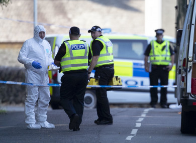 Forensic officers at the police cordon on Ardbeg Road on the Isle of Bute in Scotland