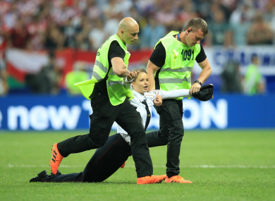 Security staff remove a pitch invader.