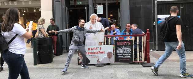 Tourists pose in front of a Pope Francis Cardboard Cut Out in front of Mary's Hardware Bar on Wicklow Street.