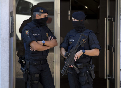 Catalan police officers stand guard at the entrance of a building during a raid, following an attack in Cornella de Llobregat.
