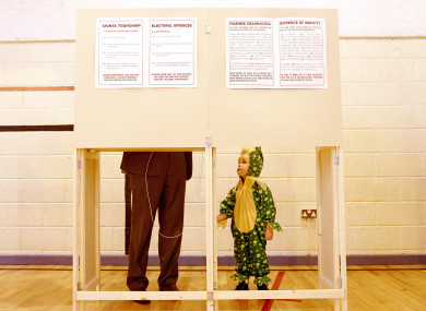 Daniel McGuire dressed up for his third birthday watches as his father Micheal casts his vote in Galway in October, 2011.