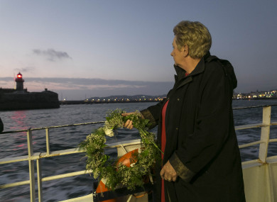Mary McCarthy, whose husband's grandfather Adam Smyth died in the sinking of the RMS Leinster, with a wreath as she leaves Dun Laoghaire.