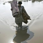 A flood survivor casts a shadow and reflection into the flood waters as he salvages belongings in Azakhel near Nowshera, northwest of Pakistan on Saturday Aug. 14, 2010. Around 1,500 people have died in the floods, which have affected directly or indirectly 14 million people, and aid workers have warned that diseases spread in the aftermath could raise the death toll.<span class=