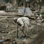 A flood survivor drinks from a water pump amid the rubble of destroyed homes in Azakhel, near Nowshera, northwest Pakistan.<span class=
