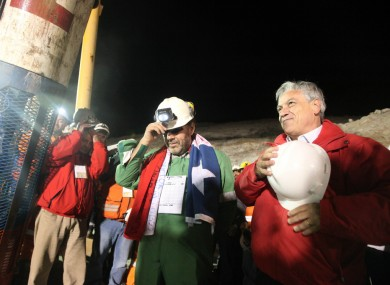 Luis Urzua, the final miner released, stands with president Sebastian Pinera as workers sing the Chilean national anthem.