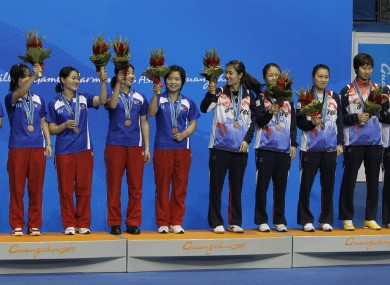 North Korean (left) and South Korean table tennis players celebrate after both teams won bronze medals in women's table tennis at the Asian Games. South Korea has reportedly said it would allow the North to hold some games in 2022.