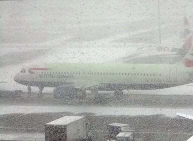 Snow showers cover Heathrow Airport in West London. Many UK airports are shut, and bus services in Ireland have been affected by poor weather.